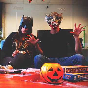 A couple sitting on a couch on a halloween party